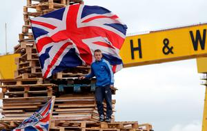 A youth stands on top of a bonfire on the Newtownards Road in east Belfast. AFP PHOTO/PAUL FAITHPAUL FAITH/AFP/Getty Images.
