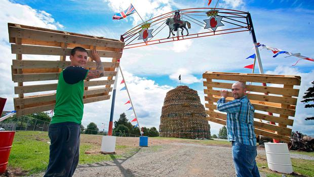 Bonfire builders Dean Neeson and Graeme Stewart carry wooden pallets to a bonfire in the Ballymacash area of Lisburn on July 10, 2017, ahead of the traditional 11th night bonfires. [Photo: Paul Faith /AFP/Getty Images]