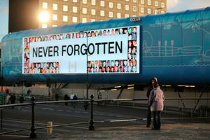 """LIVERPOOL, ENGLAND - APRIL 27:  A large bill board displays the words """"Never Forgotten"""" as people gather outside Liverpool's Saint George's Hall as they attend a vigil for the 96 victims of the Hillsborough tragedy on April 27, 2016 in Liverpool, England. The civic commemoration event marks the outcome of the fresh inquests into the 1989 Hillsborough disaster, in which 96 football supporters were crushed to death, and concluded yesterday with a verdict of unlawful killing. Relatives, Liverpool supporters and members of the public are taking part in the vigil at St George's Hall where a candle is lit for each of the 96 victims who lost their lives during a crush at the Hillsborough football ground in Sheffield, South Yorkshire in 1989..  (Photo by Christopher Furlong/Getty Images)"""