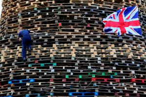 A man climbs up one of the largest 11th night Bonfires in the lower Shankill road area of Belfast, Northern Ireland on July 11, 2016, ahead of the lighting of the traditional 11th night bonfires. The Eleventh Night refers to the night before the Twelfth of July, an annual Protestant commemoration of the famous battle were Protestant King William III of Orange defeated Catholic King James II at the battle of the Boyne on July 12, 1690. / AFP PHOTO / PAUL FAITHPAUL FAITH/AFP/Getty Images