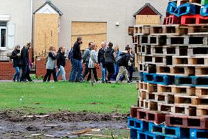 Foreign tourists take a tour past one of the largest 11th night Bonfires in the lower Shankill road area of Belfast, Northern Ireland on July 11, 2016, ahead of the lighting of the traditional 11th night bonfires. The Eleventh Night refers to the night before the Twelfth of July, an annual Protestant commemoration of the famous battle were Protestant King William III of Orange defeated Catholic King James II at the battle of the Boyne on July 12, 1690. / AFP PHOTO / PAUL FAITHPAUL FAITH/AFP/Getty Images