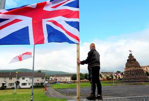 A youth balances on a fence as Union flags flutter in the breeze beside one of the largest 11th night Bonfires in the lower Shankill road area of Belfast, Northern Ireland on July 11, 2016, ahead of the lighting of the traditional 11th night bonfires. The Eleventh Night refers to the night before the Twelfth of July, an annual Protestant commemoration of the famous battle were Protestant King William III of Orange defeated Catholic King James II at the battle of the Boyne on July 12, 1690. / AFP PHOTO / PAUL FAITHPAUL FAITH/AFP/Getty Images