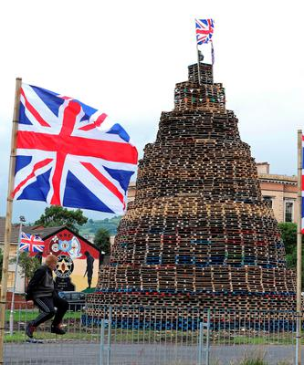 A youth balances on a fence beside one of the largest 11th night Bonfires in the lower Shankill road area of Belfast, Northern Ireland on July 11, 2016, ahead of the lighting of the traditional 11th night bonfires. The Eleventh Night refers to the night before the Twelfth of July, an annual Protestant commemoration of the famous battle were Protestant King William III of Orange defeated Catholic King James II at the battle of the Boyne on July 12, 1690. / AFP PHOTO / PAUL FAITHPAUL FAITH/AFP/Getty Images