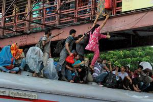 A Bangladeshi woman tries to jump onto an overcrowded train from a bridge to travel home for Eid al-Fitr in Dhaka, Bangladesh, Wednesday, Aug. 7, 2013. Muslims across the world are preparing for the arrival of Eid al-Fitr, the festival marking the end of the Muslim fasting month of Ramadan. (AP Photo/A.M. Ahad)