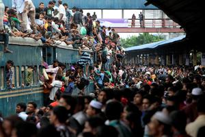 Bangladeshi Muslims make space for themselves on the roof of an overcrowded train to head home ahead of Eid al-Fitr as others wait at a railway station in Dhaka, Bangladesh, Thursday, Aug. 8, 2013. Hundreds of thousands of people working in Dhaka to make a living return home to spend time with their family during Eid al-Fitr. (AP Photo/A.M. Ahad)