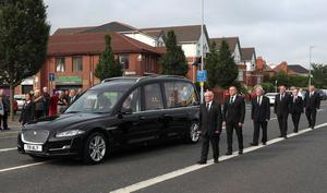 A guard of honour flanks the hearse carrying the body of leading Republican Bobby Storey to his Anderstown home in Belfast.
