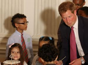 WASHINGTON, DC - MAY 09:  HRH Prince Harry (R), talks to young children during an event hosted by first lady Michelle Obama (L) to honor military families at the White House on May 9, 2013 in Washington, DC. HRH Prince Harry will be undertaking engagements on behalf of charities with which the Prince is closely associated on behalf also of HM Government, with a central theme of supporting injured service personnel from the UK and US forces.  (Photo by Mark Wilson/Getty Images)