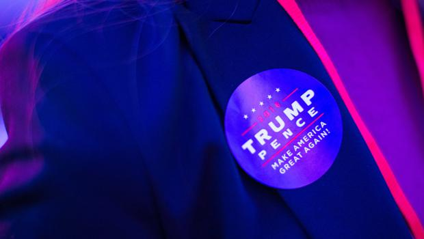 LONDON, ENGLAND - NOVEMBER 08: A guest is pictured wearing a 'Trump / Pence' sticker during a US election night party at the United States Embassy on November 8, 2016 in London, England. Americans have gone to the polls today, November 8, to elect the 45th President of the United States. Hillary Clinton represents the Democrats and, if successful, would be the first woman president in American history.  Donald Trump represents the Republicans and his campaign has been dogged by bad publicity, despite this the polls show that either of the two contenders could win with the election too close to call. (Photo by Jack Taylor/Getty Images)
