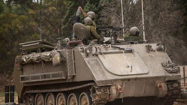 """Israeli soldiers fire mortars from an armoured personnel carrier near the Israeli-Gaza border during operation """"Protective Edge"""" on July 21, 2014 near Sderot, Israel  (Photo by Andrew Burton/Getty Images)"""