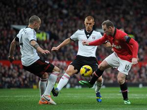 Manchester United's Wayne Rooney (right) takes on Fulham's Steve Sidwell (centre) and Johnny Heitinga during the Barclays Premier League match at Old Trafford, Manchester.