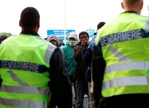 Migrants face a police cordon by the perimeter fence of the Eurotunnel site at Coquelles in Calais, France. PRESS ASSOCIATION Photo. Picture date: Thursday July 30, 2015. Nine people have been killed attempting to cross the Channel in the last month, according to Eurotunnel, as migrants try to reach Britain. See PA story POLITICS Calais. Photo credit should read: Yui Mok/PA Wire