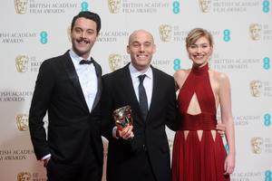 LONDON, ENGLAND - FEBRUARY 16:  Joshua Oppenheimer (C), winner of the Best Documentary award, poses with Jack Huston and Imogen Poots in the winners room at the EE British Academy Film Awards 2014 at The Royal Opera House on February 16, 2014 in London, England.  (Photo by Anthony Harvey/Getty Images)