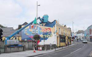 A mural is painted on Bridge Street in Balbriggan, to mark the centenary of the sacking of the town (Niall Carson/PA)