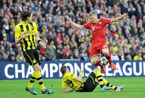 Bayern Munich's Bastian Schweinsteiger (right) is tackled by Borussia Dortmund's Kevin Grosskreutz (centre) during the UEFA Champions League Final at Wembley Stadium, London. PRESS ASSOCIATION Photo. Picture date: Saturday May 25, 2013.