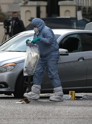 A forensic officer bags evidence after examining the silver car (Jonathan Brady/PA)
