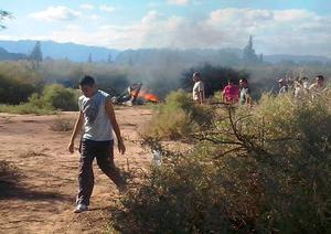 People are seen near the burning wreckages of two helicopters which collided mid-air near Villa Castelli, in the Argentine province of La Rioja, on March 9, 2015. Eight French nationals, including sports stars, filming a reality TV show were killed Monday along with two Argentine pilots when their helicopters collided in mid-air in northwestern Argentina, officials said.