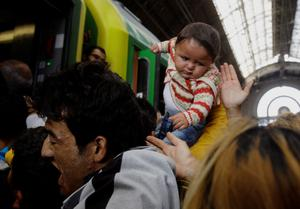 Migrants of several countries enter a local train with direction to the Hungarian-Austrian border at Keleti (East) railway station in Budapest on September 3, 2015. A train carrying between 200 and 300 migrants left Budapest's main international train station and headed toward the Austrian border, after authorities re-opened the station to migrants.  AFP PHOTO / PETER KOHALMIPETER KOHALMI/AFP/Getty Images