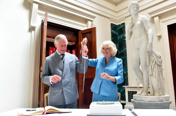 The Prince of Wales and Duchess of Cornwall slice a sponge cake resembling Mount Stewart House, in Co Down, during a tour for the official re-opening of the National Trust property, which has undergone a  refurbishment.