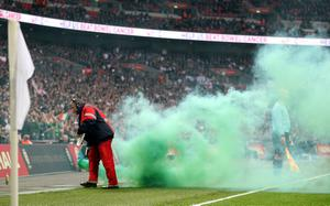A green smoke canister is removed from the pitch by a steward during the International Friendly match at Wembley Stadium, London. PRESS ASSOCIATION Photo. Picture date: Wednesday May 29, 2013. See PA story SOCCER England. Photo credit should read: Nick Potts/PA Wire. RESTRICTIONS: Use subject to FA restrictions. Editorial use only. Commercial use only with prior written consent of the FA. No editing except cropping. Call +44 (0)1158 447447 or see www.paphotos.com/info/ for full restrictions and further information.