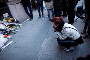 """A fan reacts at a memorial outside of the residence of British music legend David Bowie in New York on January 11, 2016. Bowie has died at the age of 69 after a secret battle with cancer, unleashing a cascade of tributes for one of the most influential and innovative artists of his time. A notoriously private person, Bowie's death in New York was a shock to the world with the announcement coming just three days after he released his 25th studio album """"Blackstar"""", on his 69th birthday on January 8. """"David Bowie died peacefully today (Sunday) surrounded by his family after a courageous 18-month battle with cancer,"""" said a statement posted January 11 on his official social media accounts. AFP PHOTO/KENA BETANCURKENA BETANCUR/AFP/Getty Images"""