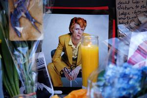 """A poster with David Bowie's face is seen at a memorial outside of the apartment building where he had a home in New York on January 11, 2016. Bowie has died at the age of 69 after a secret battle with cancer, unleashing a cascade of tributes for one of the most influential and innovative artists of his time. A notoriously private person, Bowie's death in New York was a shock to the world with the announcement coming just three days after he released his 25th studio album """"Blackstar"""", on his 69th birthday on January 8. """"David Bowie died peacefully today (Sunday) surrounded by his family after a courageous 18-month battle with cancer,"""" said a statement posted January 11 on his official social media accounts. AFP PHOTO/KENA BETANCURKENA BETANCUR/AFP/Getty Images"""