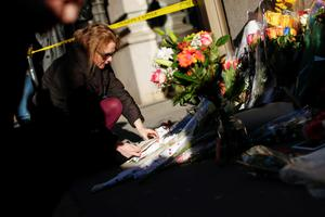 """A fan puts flowers at a memorial outside of the residence of British music legend David Bowie in New York on January 11, 2016. Bowie has died at the age of 69 after a secret battle with cancer, unleashing a cascade of tributes for one of the most influential and innovative artists of his time. A notoriously private person, Bowie's death in New York was a shock to the world with the announcement coming just three days after he released his 25th studio album """"Blackstar"""", on his 69th birthday on January 8. """"David Bowie died peacefully today (Sunday) surrounded by his family after a courageous 18-month battle with cancer,"""" said a statement posted January 11 on his official social media accounts. AFP PHOTO/KENA BETANCURKENA BETANCUR/AFP/Getty Images"""