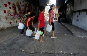 Palestinian children carry drinking water to their homes in the Nuseirat refugee camp, central Gaza Strip, Friday, July 25, 2014. (AP Photo/Hatem Moussa)