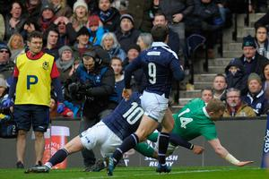 Ireland's wing Keith Earls (R) scores a try past Scotland's fly-half Finn Russell during the Six Nations international rugby union match between Scotland and Ireland at Murrayfield in Edinburgh, Scotland on Febuary 4, 2017.   / AFP PHOTO / Andy BuchananANDY BUCHANAN/AFP/Getty Images