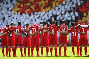 The Liverpool  players acknowledge a minutes silence for the Hillsborough victims on the 25th anniversary of the tragedy prior to the Barclays Premier League match between Liverpool and Manchester City at Anfield on April 13, 2014 in Liverpool, England.  (Photo by Alex Livesey/Getty Images)