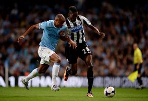MANCHESTER, ENGLAND - AUGUST 19:  Vincent Kompany of Manchester City challenges Sammy Ameobi of Newcastle United during the Barclays Premier League match between Manchester City and Newcastle United at the Etihad Stadium on August 19, 2013 in Manchester, England.  Vincent Kompany of Manchester City injured himself in the process of making the tackle and had to leave the pitch. (Photo by Michael Regan/Getty Images)