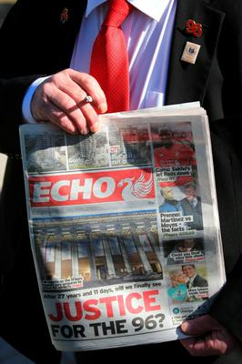 WARRINGTON, ENGLAND - APRIL 26:  A man holds up a copy of the Liverpool Echo as relatives arrive at Birchwood Park to hear the conclusions of the Hillsborough inquest on April 26, 2016 in Warrington, England. The fresh inquests into the 1989 Hillsborough disaster, in which 96 football supporters were crushed to death, began on March 31 2014 after the initial verdicts were quashed. Relatives of Liverpool supporters who died in Britain's worst sporting disaster gathered in the purpose-built court to hear the jurys verdict in Warrington after a 25 year fight to overturn the accidental death verdicts handed down at the initial 1991 inquiry.  (Photo by Christopher Furlong/Getty Images)