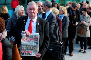 WARRINGTON, ENGLAND - APRIL 26:  A man holds up a copy of the Liverpool Echo as relatives arrive at Birchwood Park to hear the conclusions of the Hillsborough inquest on April 26, 2016 in Warrington, England. The fresh inquests into the 1989 Hillsborough disaster, in which 96 football supporters were crushed to death, began on March 31 2014 after the initial verdicts were quashed. Relatives of Liverpool supporters who died in Britain's worst sporting disaster gathered in the purpose-built court to hear the jurys verdict in Warrington after a 25 year fight to overturn the accidental death verdicts handed down at the initial 1991 inquiry.  (Photo by Dave Thompson/Getty Images)