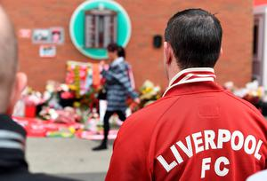 People look at the list of victims' names at the temporary Hillsborough memorial, ahead of a memorial service at Anfield in Liverpool, north west Engand on April 15, 2016, on the 27th anniversary of the Hillsborough Disaster. 96 Liverpool supporters died at the 1989 FA Cup semi-final between Liverpool and Nottingham Forest at the Hillsborough football ground in Sheffield, northern England. 2016 will be the final year a memorial service is held at Anfield. / AFP PHOTO / PAUL ELLISPAUL ELLIS/AFP/Getty Images