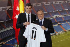 Welsh international soccer player Gareth Bale, left, and Real Madrid President Florentino Perez, pose during his official presentation at the Santiago Bernabeu stadium  in Madrid, Spain, Monday, Sept. 2, 2013, after signing for Real Madrid. The Spanish club announced Sunday that Bale has signed a six-year contract, and a person familiar with the deal said the fee was a world-record euro100 million ($132 million).  (AP Photo/Daniel Ochoa de Olza)