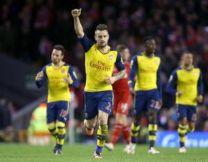 Arsenal's Mathieu Debuchy (centre) celebrates scoring his sides first goal of the game during the Barclays Premier League match at Anfield, Liverpool. Peter Byrne/PA Wire.