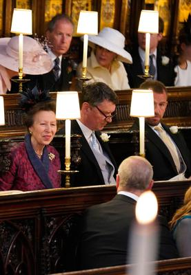WINDSOR, UNITED KINGDOM - MAY 19: Princess Anne,  Princess Royal talks to Prince Andrew, Duke of York (back to camera) as she sits alongside Sir Timothy Laurences at St George's Chapel at Windsor Castle before the wedding of Prince Harry to Meghan Markle on May 19, 2018 in Windsor, England. (Photo by  Jonathan Brady - WPA Pool/Getty Images)