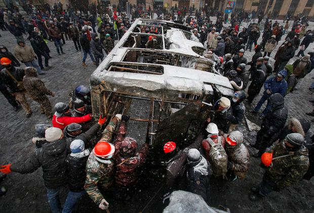 Opposition supporters move a bus  torched by protesters overnight to build a new barricade in central Kiev, Ukraine, Tuesday, Jan. 21, 2014. Opposition leader Vitali Klitschko headed for talks with the Ukrainian president on Tuesday after yet another night of violent street clashes between anti-government protesters and police. (AP Photo/Sergei Grits)