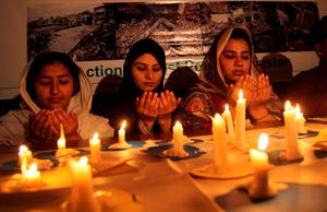 "Pakistani residents pray during a candle light vigil for the victims of Nepal earthquake in Multan on April 27, 2015. Nepalis started fleeing their devastated capital after an earthquake killed more than 3,800 people and toppled entire streets, as the United Nations prepared a ""massive"" aid operation. With fears rising of food and water shortages, people were also rushing to stores and petrol stations to stock up on supplies in the capital, ripped apart by Saturday's 7.8-magnitude quake. AFP PHOTO/ SS MIRZASS MIRZA/AFP/Getty Images"