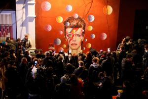 LONDON, ENGLAND - JANUARY 11: Members of the media and public gather by a mural of David Bowie in Brixton on January 11, 2016 in London, England. British music and fashion icon David Bowie died earlier today at the age of 69 after a battle with cancer. (Photo by Carl Court/Getty Images)