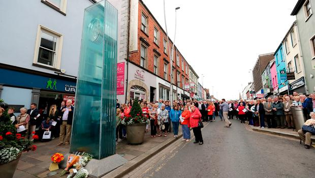 People observe a minutes silence on Market Street, Omagh, during the ceremony to mark the 20th anniversary of the Omagh bombing on 15 August 1998. PRESS ASSOCIATION Photo. Picture date: Wednesday August 15, 2018. The worst single atrocity of the Northern Ireland conflict killed 29, including a woman pregnant with twins. See PA story ULSTER Omagh. Photo credit should read: Niall Carson/PA Wire