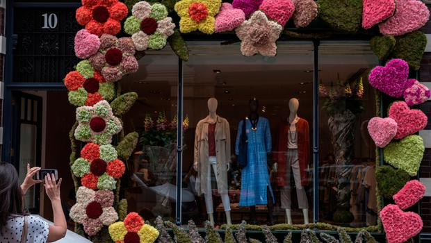 LONDON, ENGLAND - MAY 21:  A woman takes photos of a floral display outside a clothing shop during the Chelsea in Bloom floral art show on May 21, 2018 in London, England. This year is the 13th Chelsea in Bloom and the theme is 'Summer of Love', inspired by the Royal Wedding and the 1960's/70's cultural revolution. The floral show is also a competition that is entered by various Chelsea retailers, restaurants and hotels with entries being judged by an expert panel.  (Photo by Chris J Ratcliffe/Getty Images)