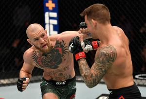 Conor McGregor punches Dustin Poirier in a lightweight fight during the UFC 257 event inside Etihad Arena on UFC Fight Island on January 23, 2021 in Abu Dhabi, United Arab Emirates. (Photo by Jeff Bottari/Zuffa LLC via Getty Images)