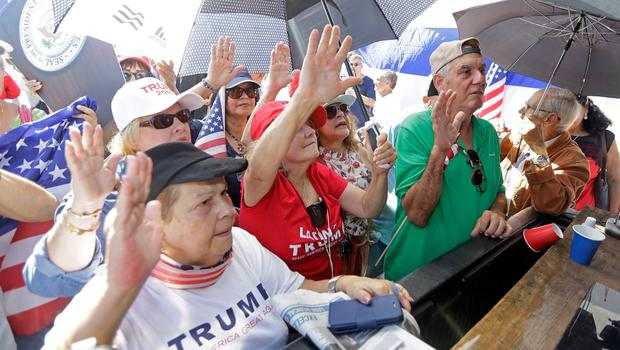 Cuban-American supporters raise their right hands as they watch on television President Donald Trump being sworn in as the 45th president of the United States.Friday, Jan. 20, 2017, in the Little Havana area in Miami. (AP Photo/Alan Diaz)