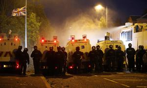 Riot police deploy a water cannon after being attacked by loyalist protesters in north Belfast, Northern Ireland, Saturday, July 13, 2013.  Hundreds of police reinforcements from Britain were deployed on Belfast's rubble-strewn streets Saturday after Protestant riots over a blocked march left 32 officers, a senior lawmaker and at least eight rioters wounded.  (AP Photo/Peter Morrison)