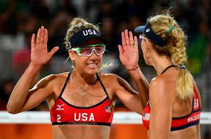 USA's April Ross (L) and Kerri Walsh Jennings celebrate after winning the women's beach volleyball qualifying match between the USA and China at the Beach Volley Arena in Rio de Janeiro late on August 8, 2016, for the Rio 2016 Olympic Games. / AFP PHOTO / Leon NEALLEON NEAL/AFP/Getty Images