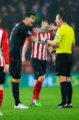 Liverpool's Dejan Lovren is booked by referee Kevin Friend on his return to Southampton during the Barclays Premier League match at St Mary's, Southampton. Chris Ison/PA Wire.