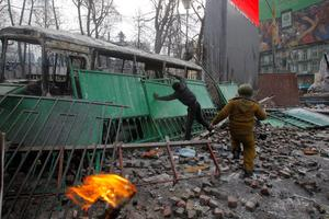 Protesters throw Molotov cocktails during unrest in central Kiev, Ukraine, Monday, Jan. 20, 2014. Protesters erected barricades from charred vehicles in central Kiev as the sound of stun grenades pierced the freezing air, after a night of rioting. (AP Photo/Sergei Grits)