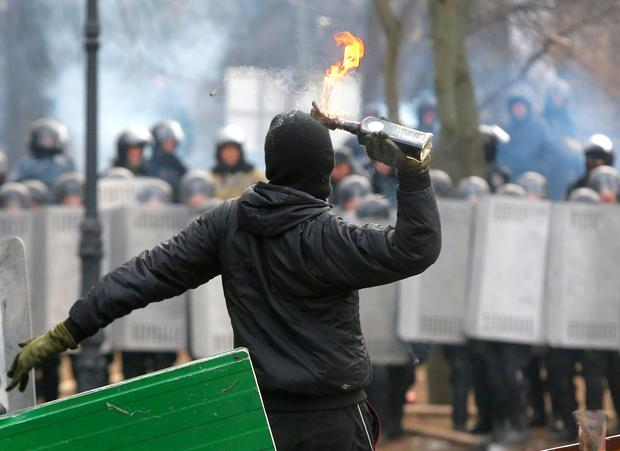 A protester throws a Molotov cocktail during unrest in central Kiev, Ukraine, Monday, Jan. 20, 2014. After a night of vicious streets battles, anti-government protesters and police clashed anew Monday in the Ukrainian capital Kiev. Hundreds of protesters, many wearing balaclavas, hurled rocks and stun grenades and police responded with tear gas. (AP Photo/Sergei Grits)