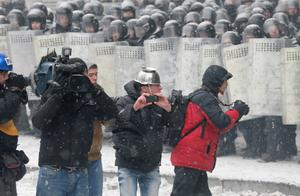Reporters take pictures during clashes between protesters  and police in central Kiev, Ukraine, Wednesday, Jan. 22, 2014. Three people have died in clashes between protesters and police in the Ukrainian capital Wednesday, according to medics on the site, in a development that will likely escalate Ukraine's two month-long political crisis. The mass protests in the capital of Kiev erupted after Ukrainian President Viktor Yanukovych spurned a pact with the European Union in favor of close ties with Russia, which offered him a $15 billion bailout. (AP Photo/Efrem Lukatsky)