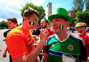 Northern Ireland fans apply facepaint outside the stadium, as Wales fans walk behind them, prior to the round of 16 match at the Parc de Princes, Paris.  Jonathan Brady/PA Wire.